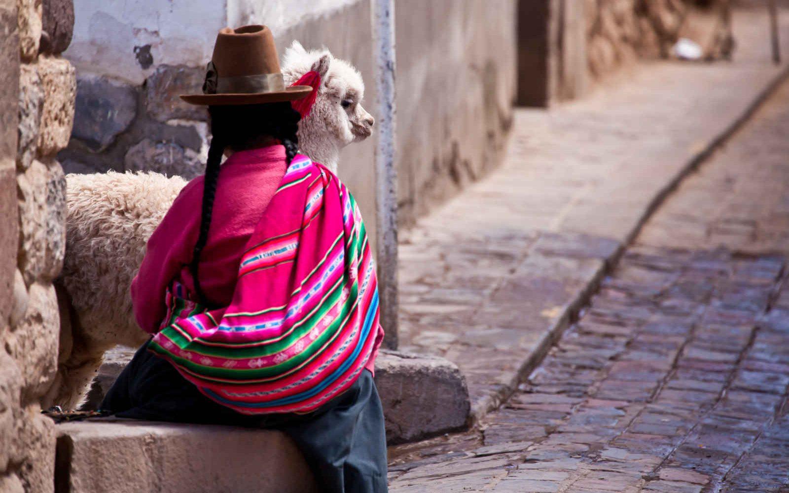 Femme et lama dans une ruelle de Cuzco, Pérou