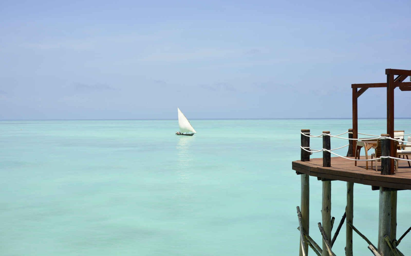 Jetée en bois sur la mer avec vue sur un Dhow, Zanzibar, Tanzanie